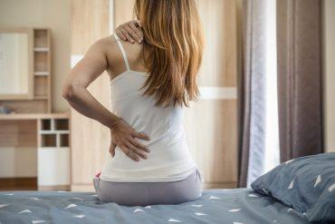 Femme assise sur un lit et se tenant le dos